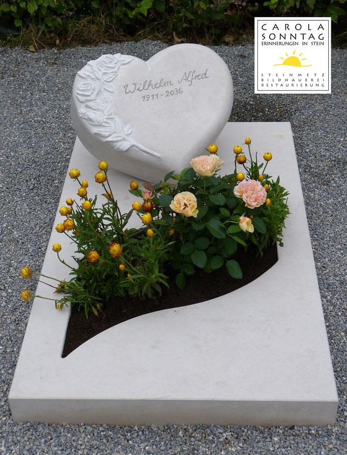 Urnengrab in hellem Naturstein mit Herz