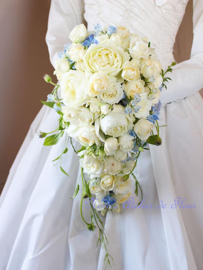 生花の白いバラとブルーのデルフィニウムのキャスケードブーケ