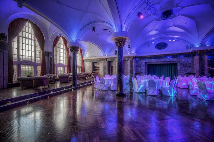 Impressionen aus dem Festsaal des Wartesaals am Dom - Runde Banketttische neben einer freien Tanzfläche mit Partybeleuchtung und Blick auf die Fensterfront
