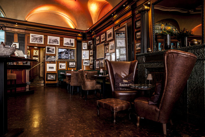 Impressionen aus dem Restaurant Wartesaal am Dom - Sessel und Vierertische vor der Bild-behangenen Wand
