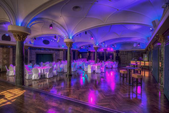 Impressionen aus dem Festsaal des Wartesaals am Dom - Runde Banketttische neben einer freien Tanzfläche mit Partybeleuchtung