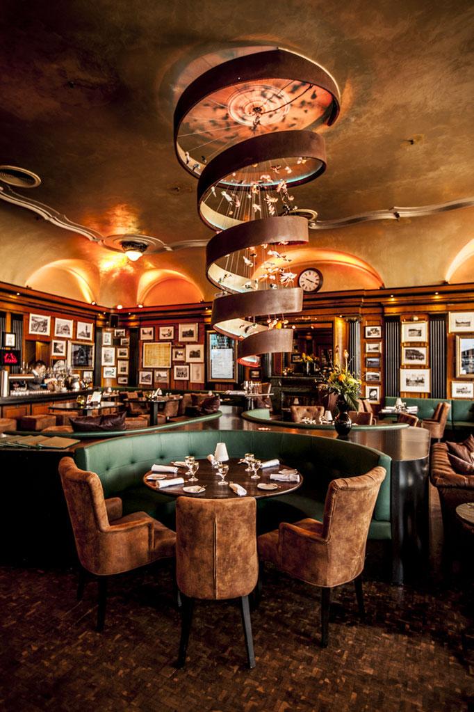 Impressionen aus dem Restaurant Wartesaal am Dom - Die ikonische Spiralen-Lampe über einem eingedeckten Tisch