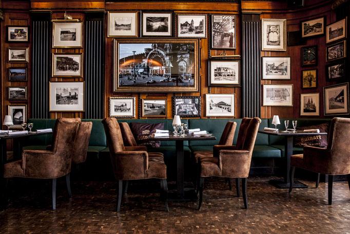 Impressionen aus dem Restaurant Wartesaal am Dom - Ein Tisch für vier Personen vor der Bild-behangenen Wand