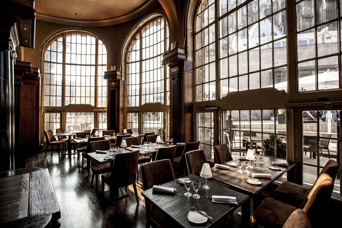 Impressionen aus dem Restaurant Wartesaal am Dom - Eingedeckte Tische an hoher Fensterfront