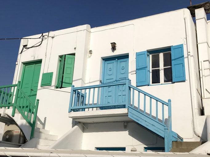Bild: Kubisches Haus auf Mykonos mit grünen und blauen Treppenaufgängen und Fensterrahmen