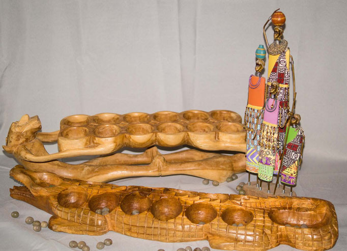"""L'Awalé est un """"jeu de planche"""" (mancala).  De nos jours, l'Awalé se rencontre dans toutes les régions de l'Afrique. Les règles de l'Awalé sont simples et varie selon les pays"""