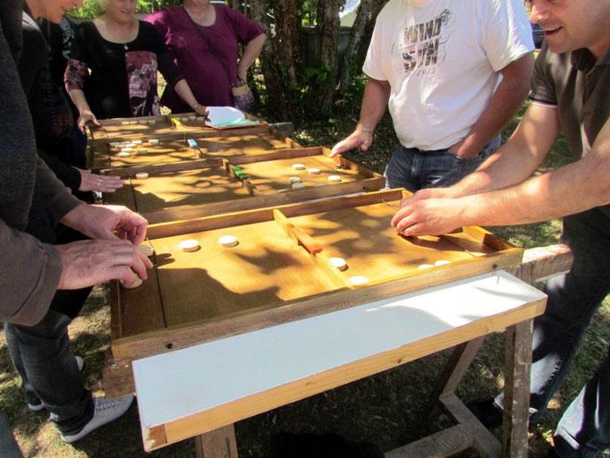 Table à élastique : jeu de rapidité et d'adresse . L'objectif est de vider son camp de tous les palets en les envoyant chez son adversaire à l'aide d'un élastique
