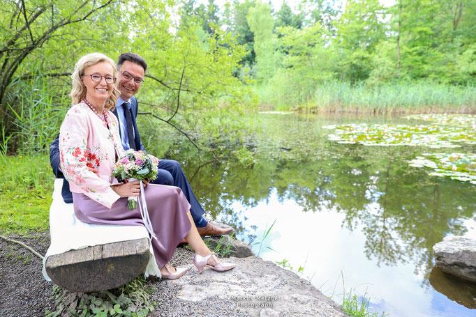 Hochzeit im Rems-Murr-Kreis, Brautpaar am See in Althütte am Bühlhauweiher sitzend, in freier Natur, Fotograf Markus Metzger, Sommer 2021, www.markus1.de