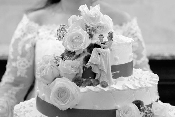 Hochzeitstorte mit Braut im Hintergrund