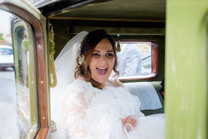 Braut lacht im Hochzeitswagen