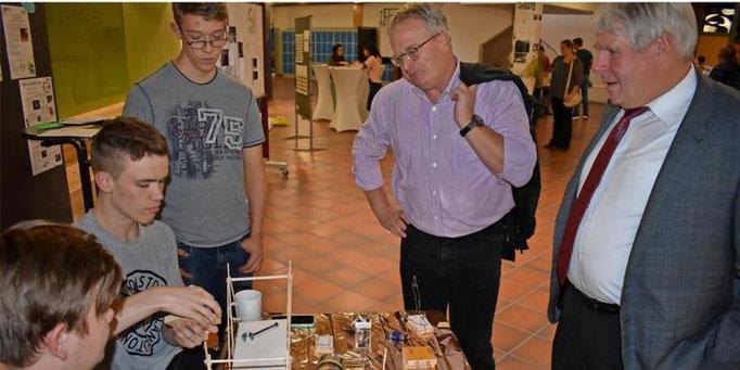 Joshua (von links) und Lucas präsentieren dem kommenden Sehnder Bürgermeister Olaf Kruse und dem noch amtierenden Amtsinhaber Carl Jürgen Lehrke ihre kleinen Erfindungen.