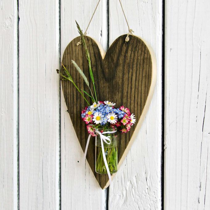Herz aus Altholz mit Vase darin Gänseblümchen und Vergissmeinnicht