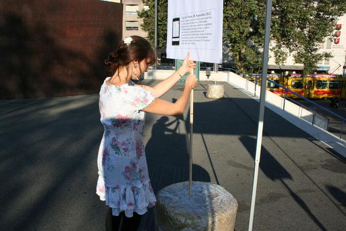 Alisha Stöcklin plaziert ein Gedichtplakat auf dem Theaterplatz.