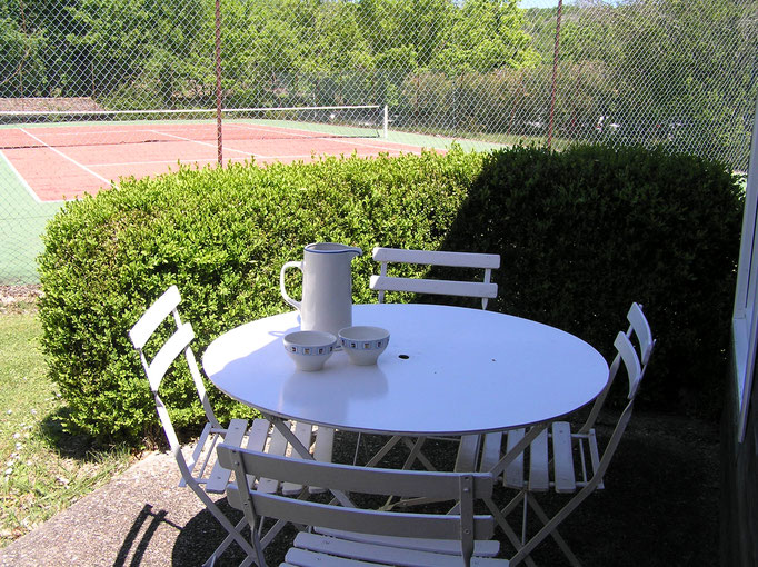 Terrasse ombragée d'une petite maison à louer face au cours de tennis du Golf des Roucous