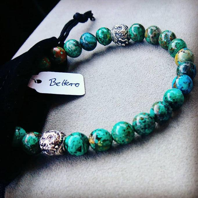 ein grünes Shenlong BEHERO Armband welches halb aus einem schwarzen Samtbeutel herrausragt