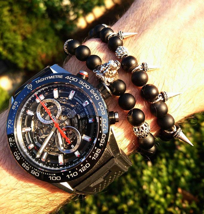 zwei schwarze BEHERO Armbänder welche neben einer TAG Heuer Uhr an einem Handgelenk getragen werden
