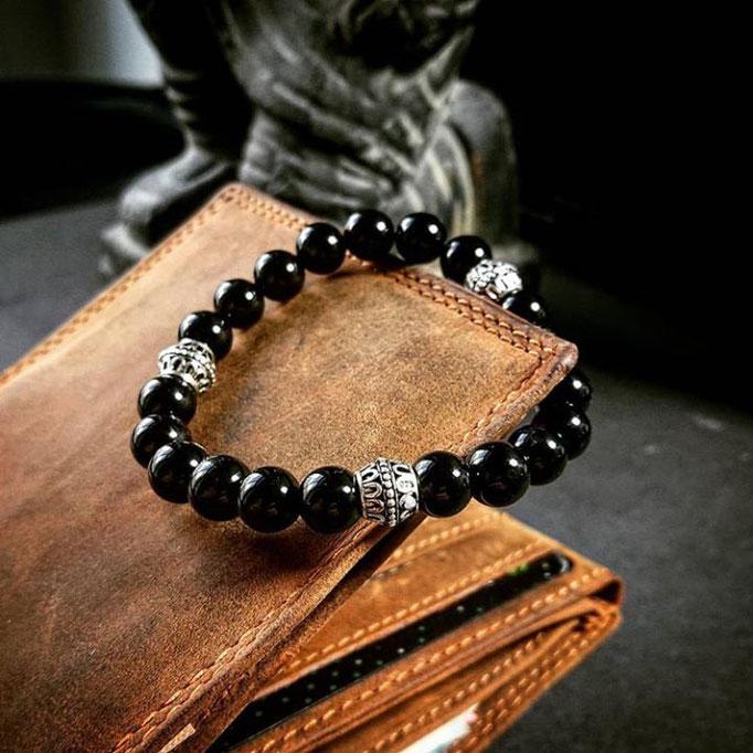 ein schwarzes BEHERO Gate Armband, welches auf einem braunen Leder Portemonnaie liegt