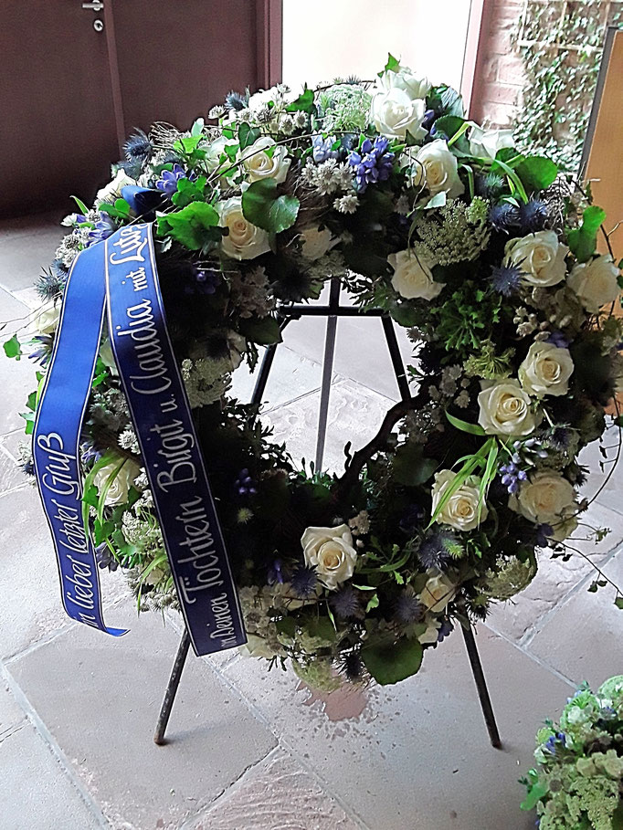 Trauerkranz rundgesteckt in weiß-blau mit Rosen