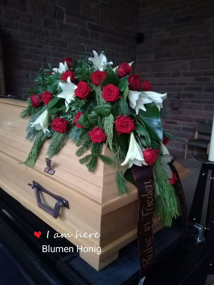 Sargbukett mit roten Rosen und weißen Lilien