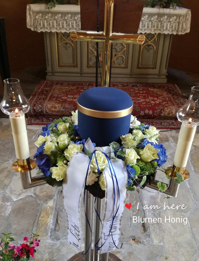 Urnenkranz mit blauen Hortensien und weißen Rosen