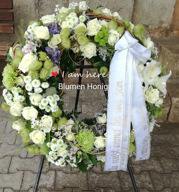 Trauerkranz rundgesteckt in weiß-grün mit Rosen und Chrysanthemen