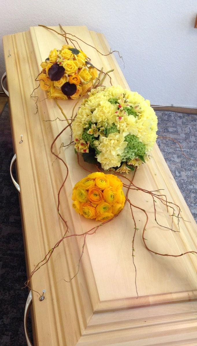 Extravaganter Sargschmuck mit Blütenkugeln in verschiedenen Gelbtönen