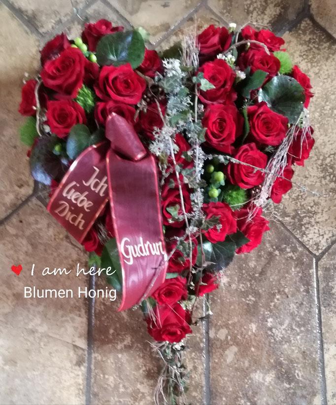 Herz gesteckt mit roten Rosen und bemoosten Schlehenzweigen