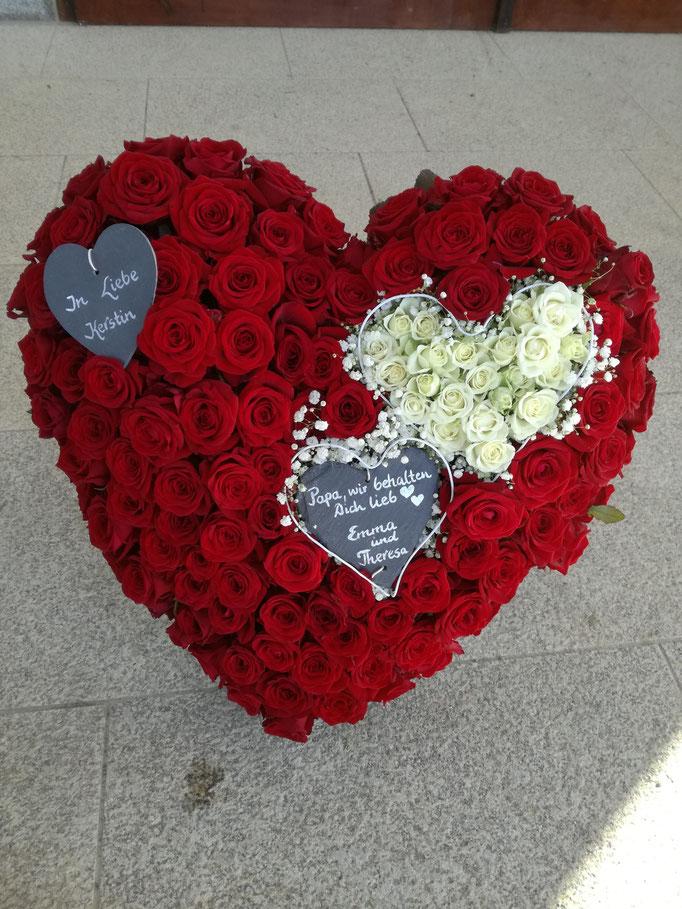 Herz mit roten Rosen Kopf an Kopf gesteckt mit kleinem Herz mit weißen Polyantha-Rosen und Schieferherzen