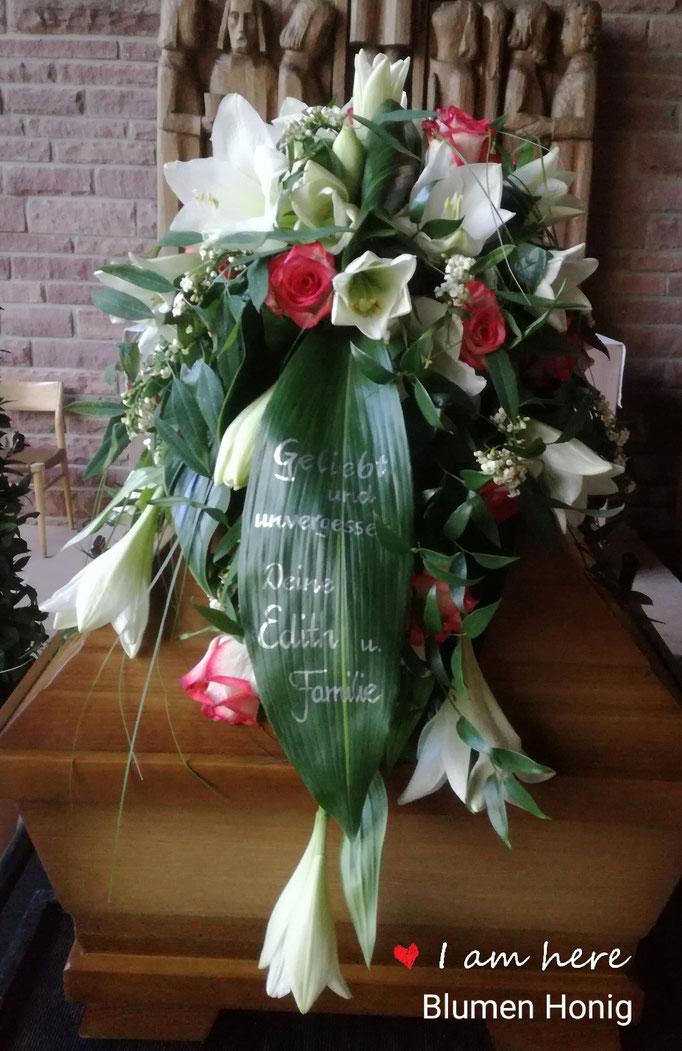 Sargbukett mit weißen Lilien und zweifarbigen Rosen