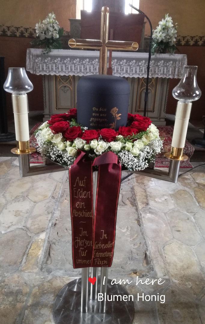 Urnenkranz mit großen roten Rosen und weißen Polyantharosen und Schleierkraut
