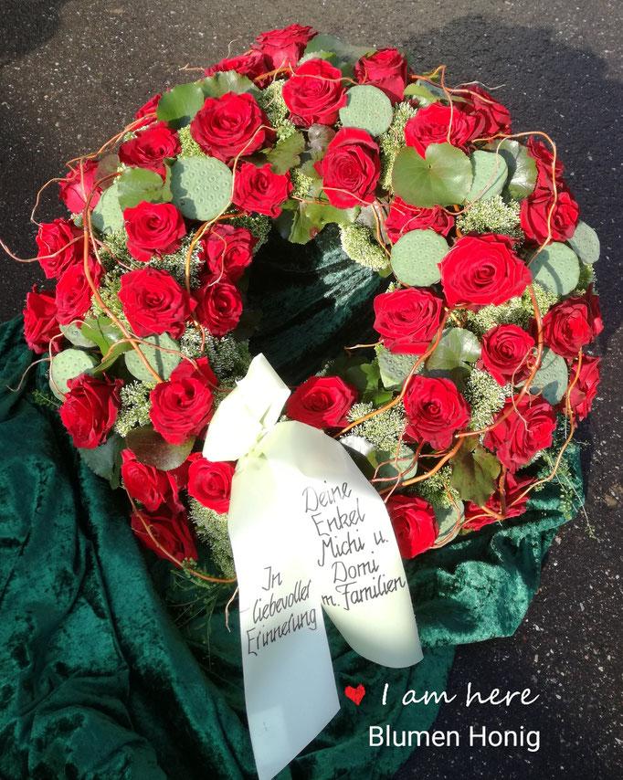 Trauerkranz mit roten Rosen rundgesteckt