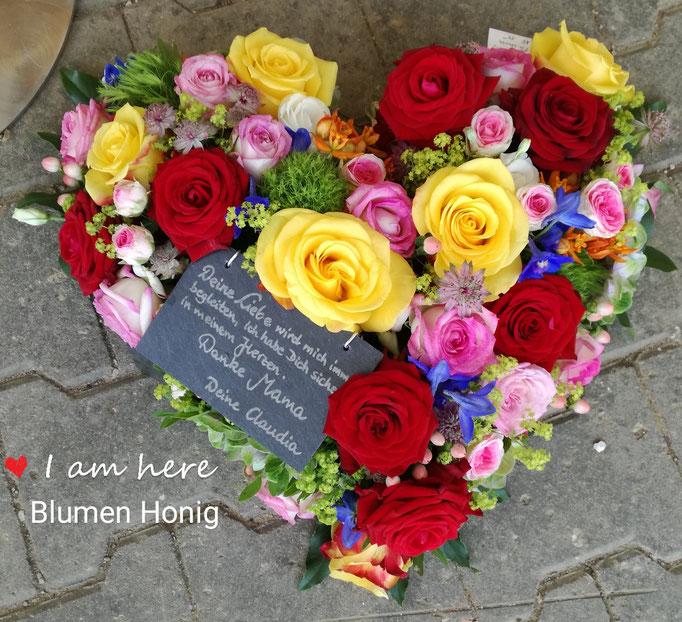 Herz gesteckt mit kräftig bunten Blüten und Schiefertafel
