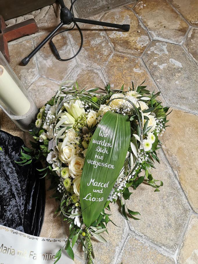 Trauerherz mit weißen Blumen und Aspidistrablatt beschriftet