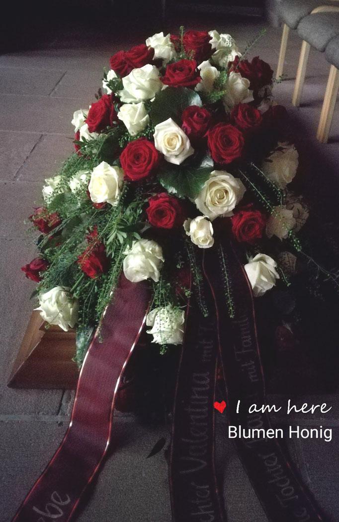 Sargschmuck mit roten und weißen Rosen