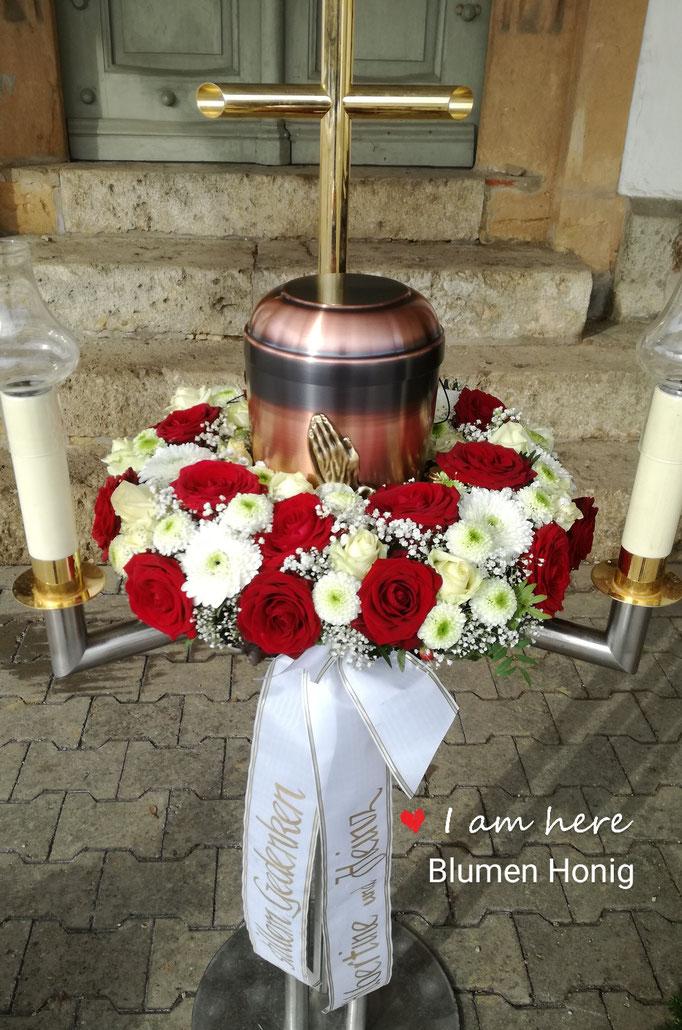 Urnenkranz mit roten Rosen und weißen Blumen