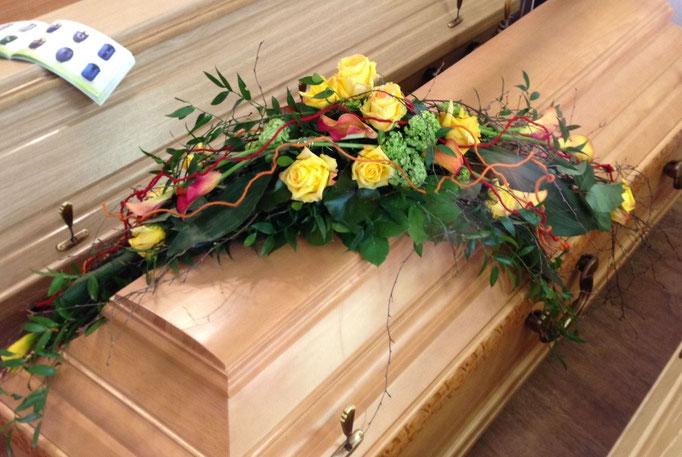 Asymmetrisch angeordnetes Sarggesteck in frühlingshaften Gelbtönen mit Rosen, Calla und Schneeball