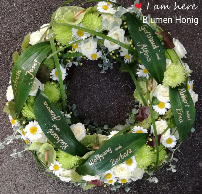 Trauerkranz rundgesteckt in grün-weiß und Blätter beschriftet