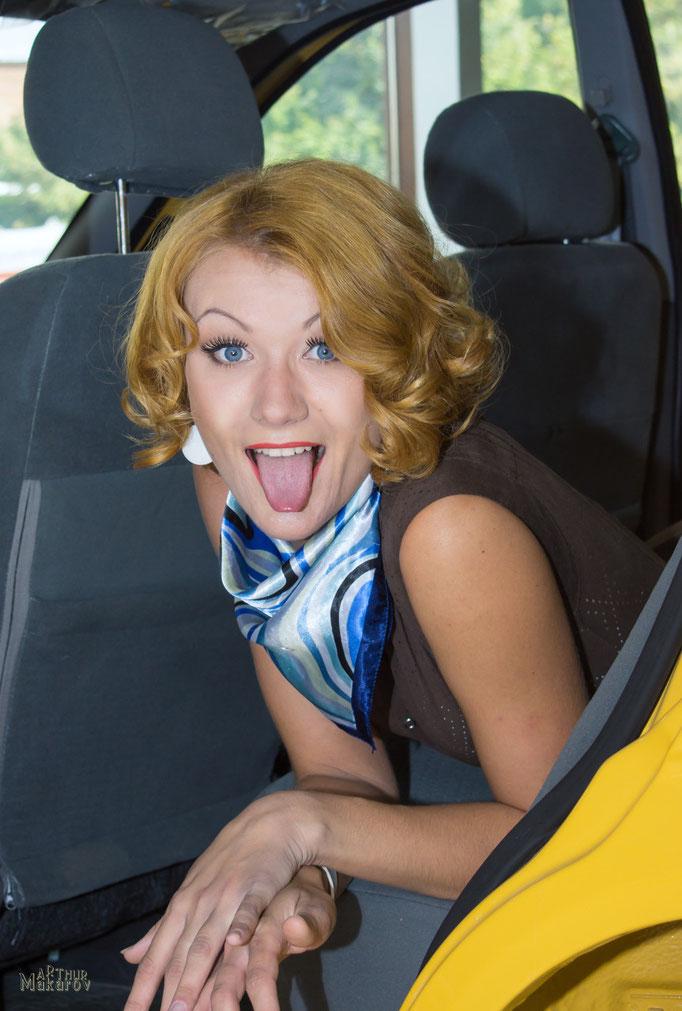 шутливый женский портрет в магазине автомобилей