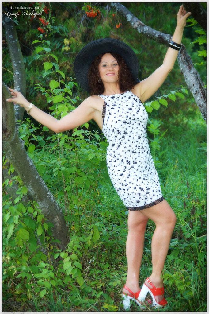 Девушка позирует на фоне деревьев