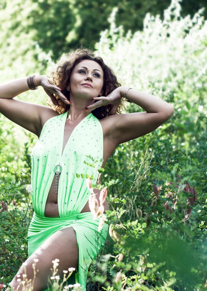 Портрет девушки на фоне зелени в солнечных лучах
