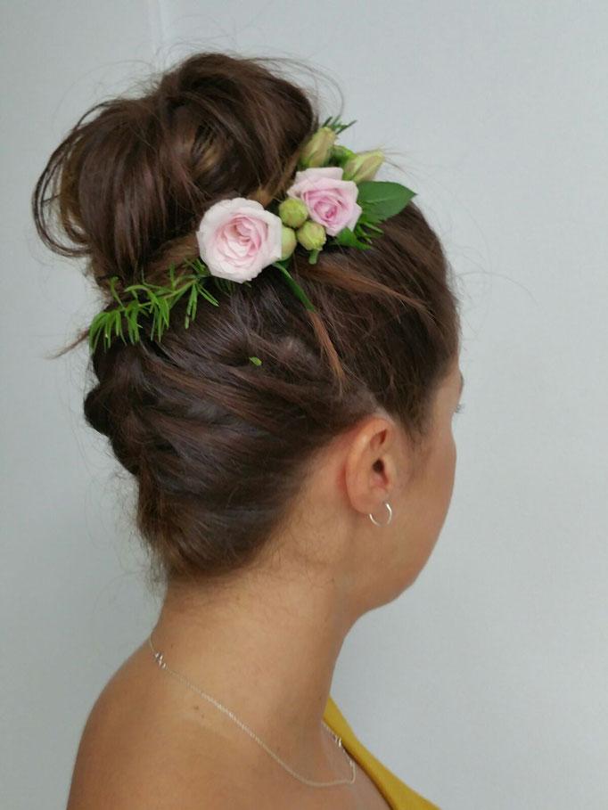 Recogido alto con trenza posterior y flor natural.