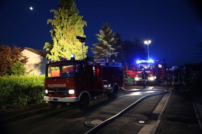 Blick auf das Brandhaus mit Feuerwehreinsatzkräften