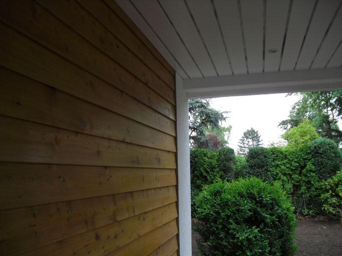 Dachüberstand sowie Lärchenholzfassade im Eingangsbereich