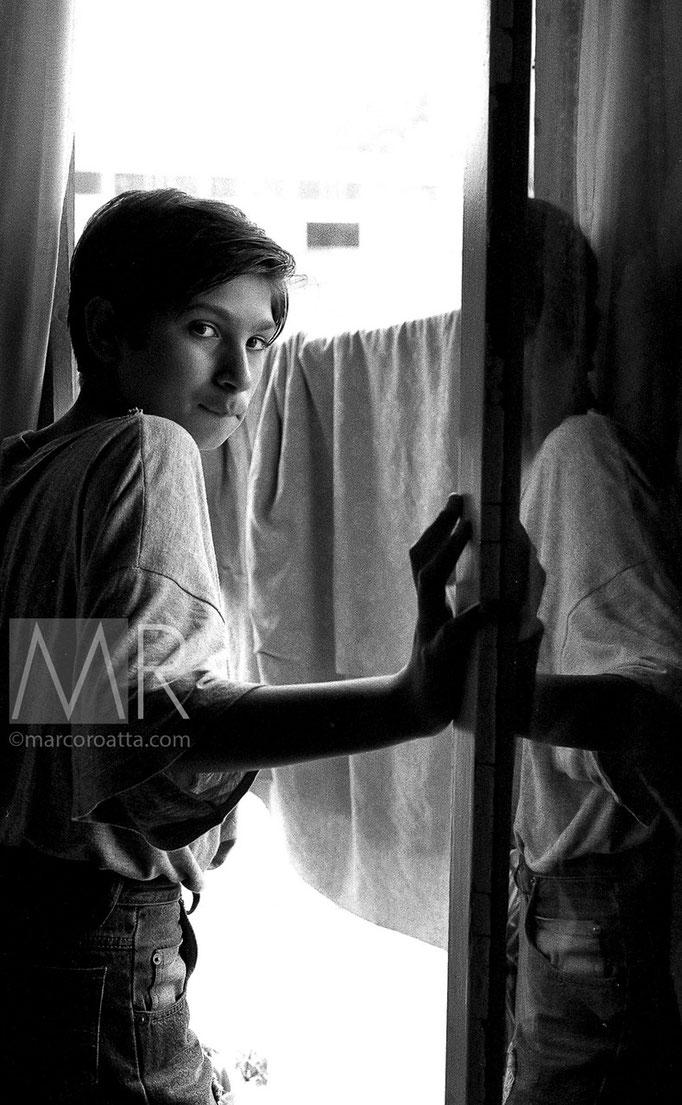 Un ragazzo osserva le demolizioni dalla finestra, sa che di lì a qualche mese anche la sua casa sarà demolita - Torino