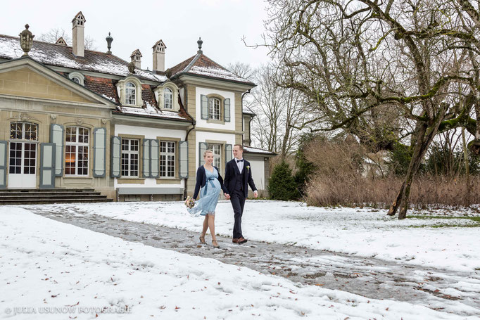 Brautpaar läuft durch den Schnee im Winter am Schloss Bümpliz in Bern