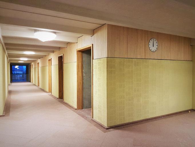 Der Schulhausflur im Obergeschoss. Man beachte die vielen Unterzüge aus Beton und die Präzisionsarbeit des hashtag-Team.