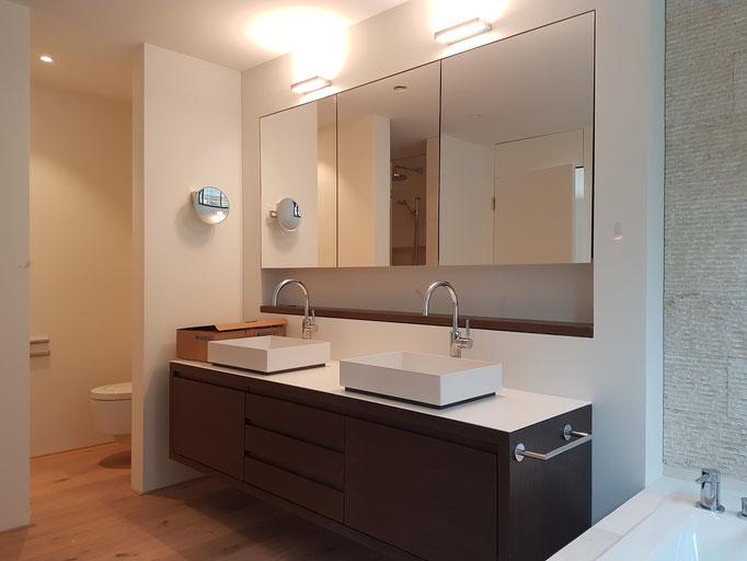 Im Badezimmer findet sich ein in Mooreiche furnierter Unterbau sowie der passende Spiegelschrank dazu.