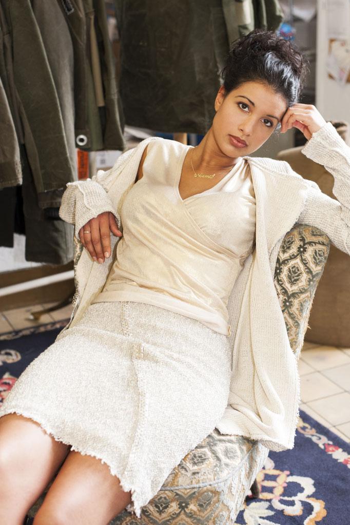 Noemi trägt  eine lange Strickjacke aus Baumwolle, 198€ dazu ein goldenes Top aus Viskose, Auflage 5 Stück- 129€ und einen Bouclérock aus Baumwolle/ Elasthan mit Goldnetz,159€
