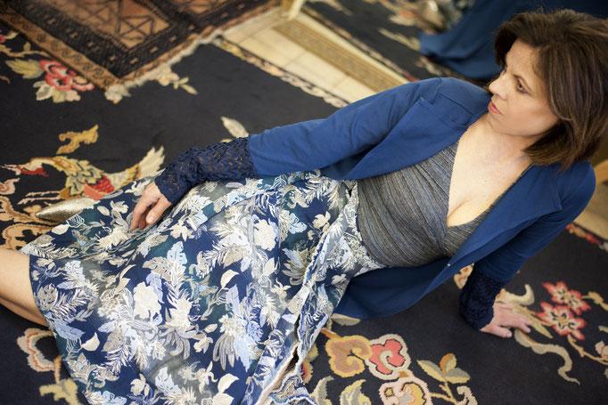 Petra trägt einen Wickelrock aus Jaquardgewebe in Blautönen, Baumwolle, Auflage: 3 Stück! 229€Dazu ein Wickeltop aus Baumwolle/ Leinen , Unikat- ausverkauft!- 159€BasicPlus Jacke aus 95% Biobaumwolle (GOTS) und 5% Elasthan, 159€