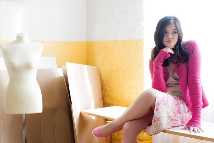 Melanie trägt  eine Strickjacke aus Merinowolle, Auflage 3 Stück, 229€; einen ausgestellten Tupfenrock mit Spitzenbund, Auflage 3 Stück, 159€ und ein Wickeltop aus Baumwolle, 129€ und rosa Ballerinas von ETHLETICS, 59€